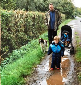 Dad, kids, springer spaniel walking in countryside