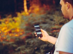 Person using a smartphone in the forest
